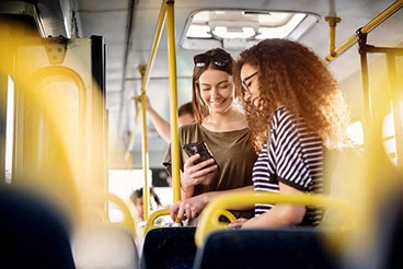Passengers on bus looking at their phones